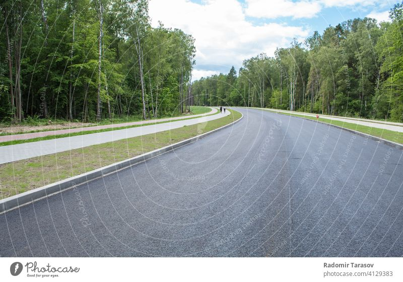 new modern road through the forest outdoor travel asphalt view highway nature transport landscape green line beautiful transportation speed sky summer traffic