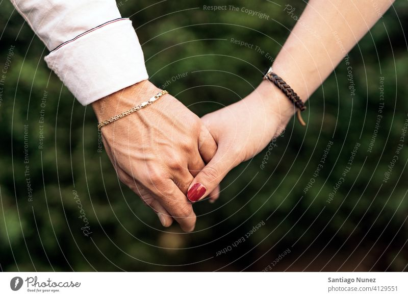 Couple Holding Hands Closeup closeup close up couple relationship holding hands together lovely front view background two family outdoors outside park nature