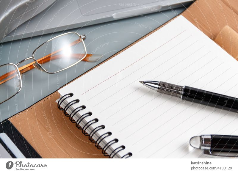 Opened agenda and pen on a grey close up Business opened write laptop planner office desk glasses smart working device gadget Modern Businessman Indoors
