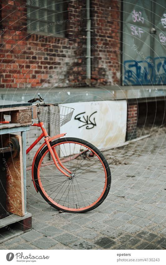 Orange bicycle in an industrial warehouse district in Hamburg Germany Oberhafen bike brick wall commute dirty germany gray grey hamburg industrial style orange