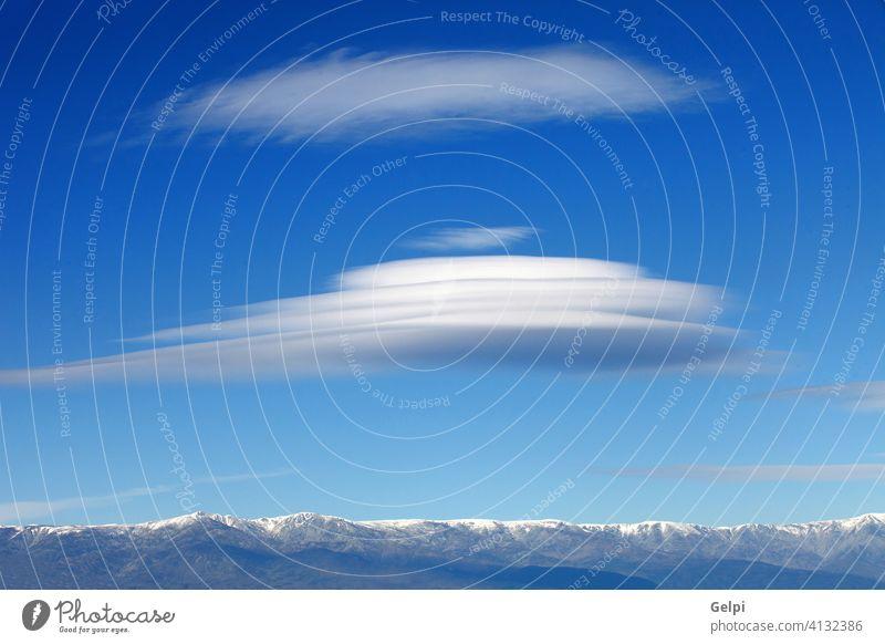 Big lenticularis cloud and snowed mountain altocumulus sky landscape peak clouds scenery wind spain unusual travel nature blue high altitude view meteorology