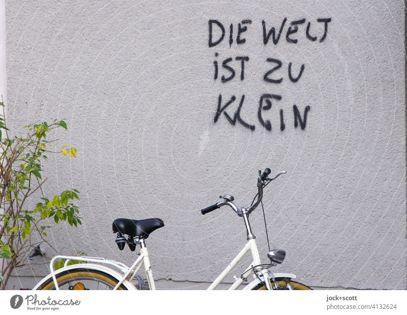 The world is too small Plaster Wall (building) Spray German saying Street art Daub Bicycle Parking area shrub Ladies bike Figure of speech Authentic Coincidence