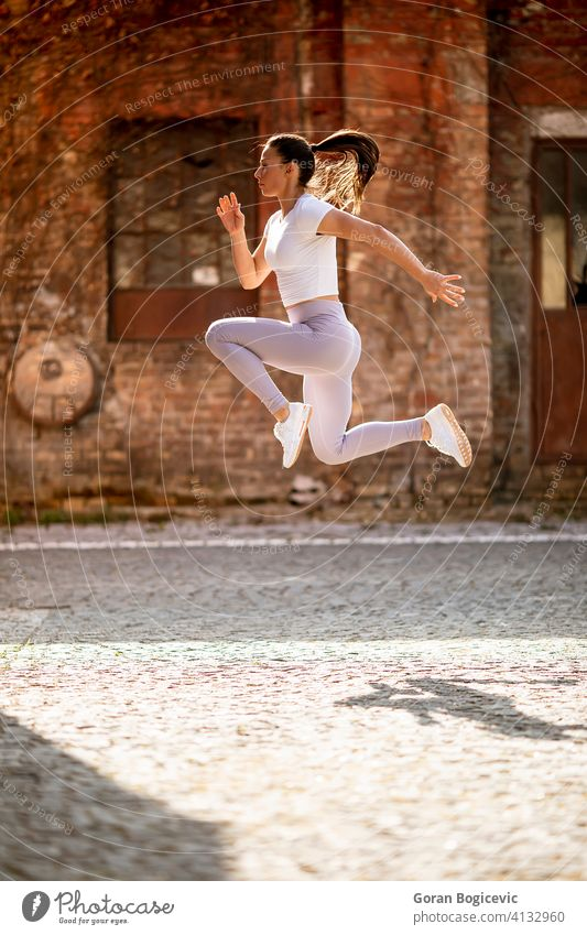 Young woman juping high during training in the urban environment city young fit fitness female jump athlete workout sport athletic activity caucasian exercise