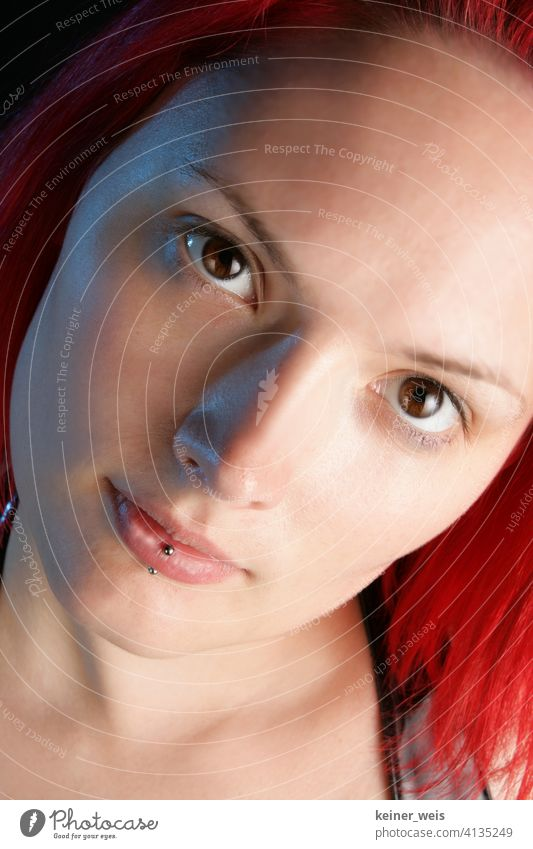 Face of young woman with piercing in lower lip and red hair Woman Piercing Young woman brown eyes Red-haired Portrait format portrait Lower lip Lip piercing