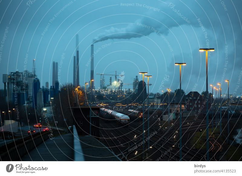 Industrial landscape with freight trains, industrial plants and blue hour lighting. Industry, logistics, rail traffic Industrial district Freight trains