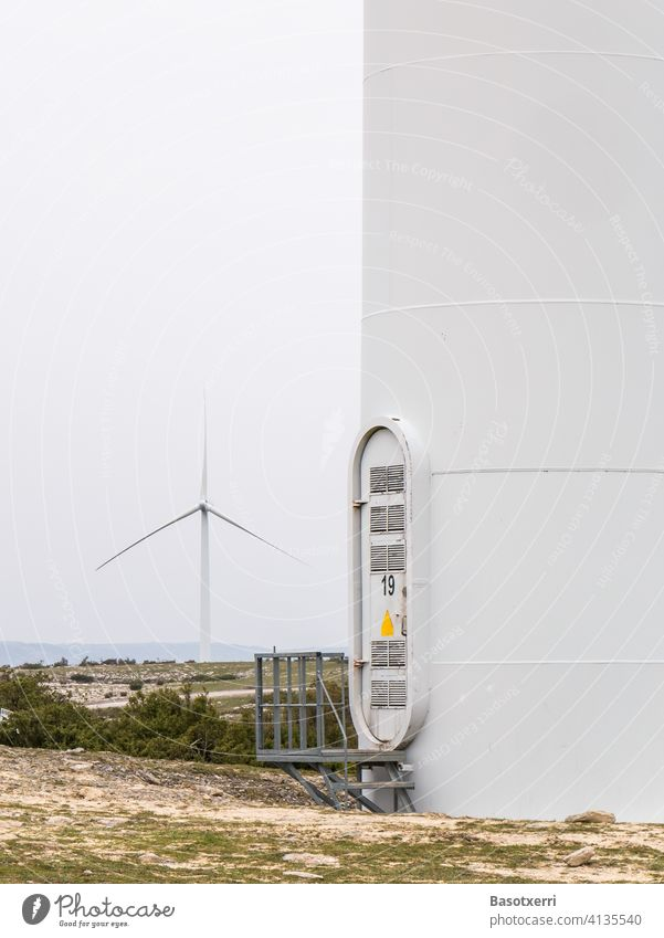 Close-up of a wind farm in the mountains of northern Spain - tower with entrance/ascent, another wind turbine in the background Wind energy plant Tower Entrance