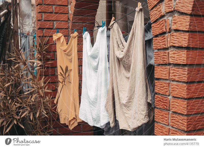 washed clothes man shirts hanging in front of house orange yellow pastel baby babyhood background blue childcare childhood clean clothespin clothing color
