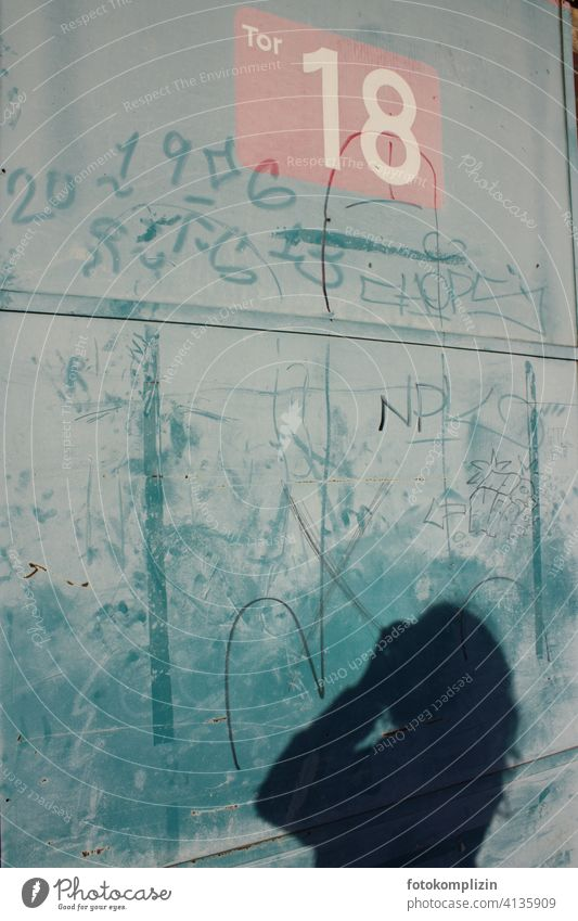 Shadow of a woman taking pictures at a goal wall Goal Wall (building) 18 number Take a photo taking a photograph Graffiti Daub Woman Characters Barred Closed
