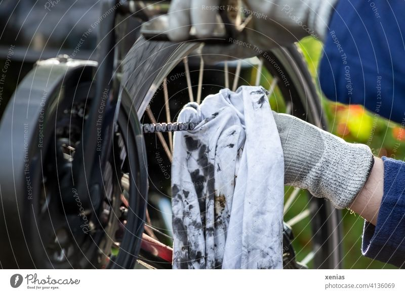 Hands in gloves clean a bicycle chain with stained oil-smeared rags, while the bike is upside down and a pedal is moved Bicycle Bicycle chain Wheel cleaning