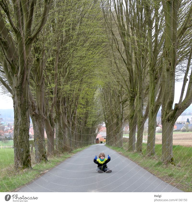 Child sits in the middle of the untraveled street of an avenue and gives the thumbs up Human being Schoolchild Street Avenue Asphalt Sit Spring Tree Field