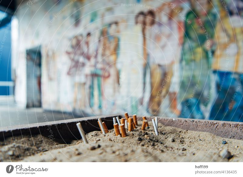 squeezed out butts in the sand in front of painted wall Cigarette Butt Smoking Tobacco products Filter-tipped cigarette Ashes tilt Unhealthy Smoke Ashtray