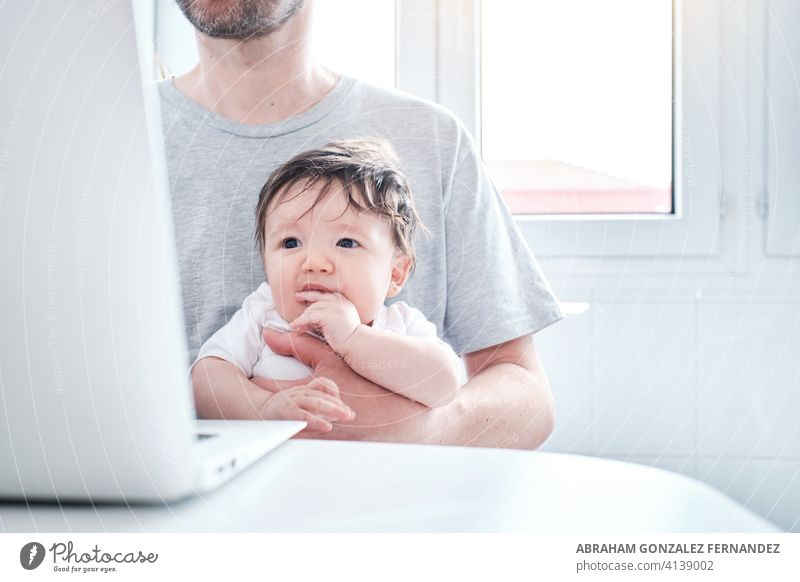 father working from home using laptop while caring for baby daughter family mother apartment parent man child busy people computer adult entrepreneur girl