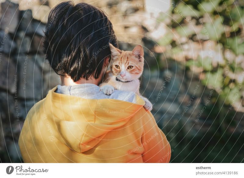 Back view of child with kitten kid pet cat pets love domestic stray homeless adorable people toddler baby lost outdoor small alone urban curiosity little street