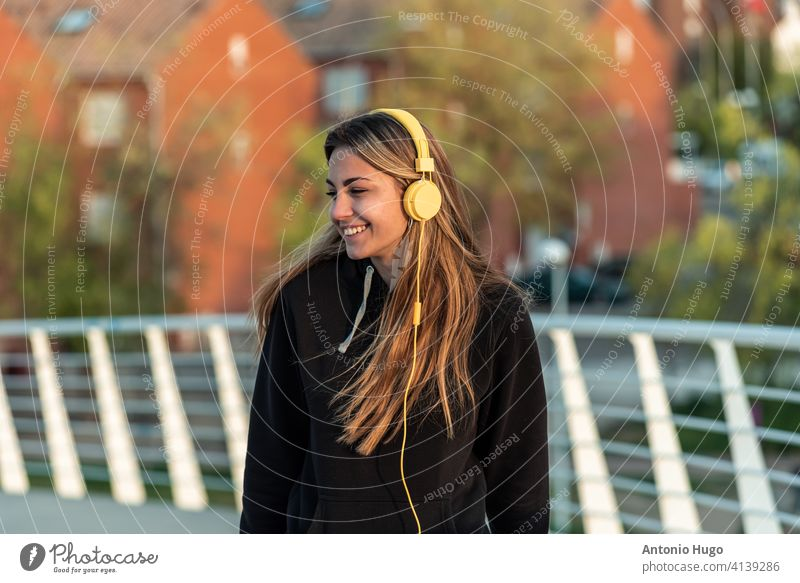 Teenage blonde girl with yellow headphones listening to music while walking on a white urban bridge. Residential buildings in the background. teenage