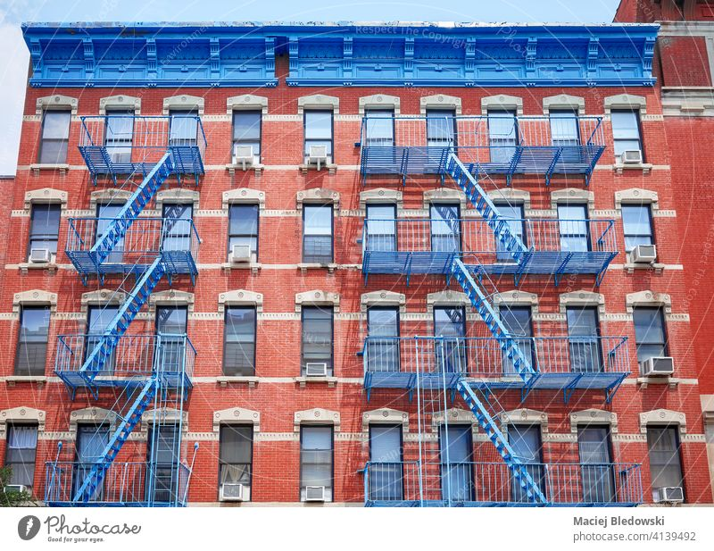Old red brick building with blue iron fire escapes, New York City, USA. city Manhattan old house apartment architecture stairs facade NYC ladder view