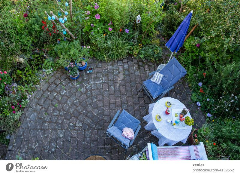 Bird's eye view in summer: Two yellow cups of coffee on the table, chairs with comfortable cushions and a parasol are ready on the terrace. This is surrounded by green plants with colorful flowers. Where have the coffee drinkers gone?