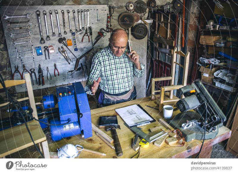Carpenter in his workshop top view carpenter man mobile senior talking business custom made work bench mature tablet male carpentry writing wood worker plans