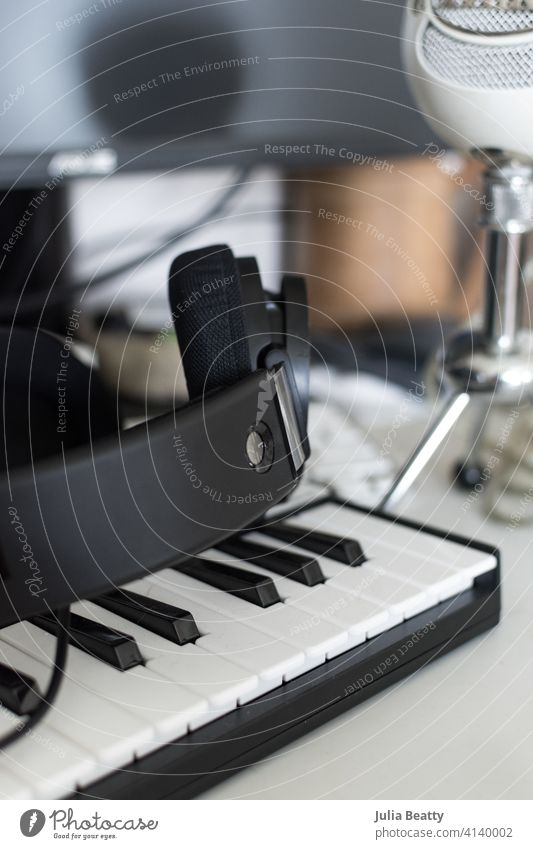 Musician's computer desk setup: keyboard, headphones, and microphone in front of a monitor music equipment dj audio technology sound studio office business