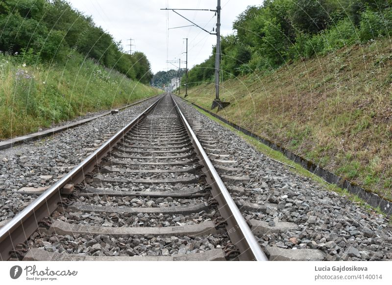 Railroad tracks in ditch lined by electric posts stretching into the distance. background column concept day direction distant far gravel green horizon industry