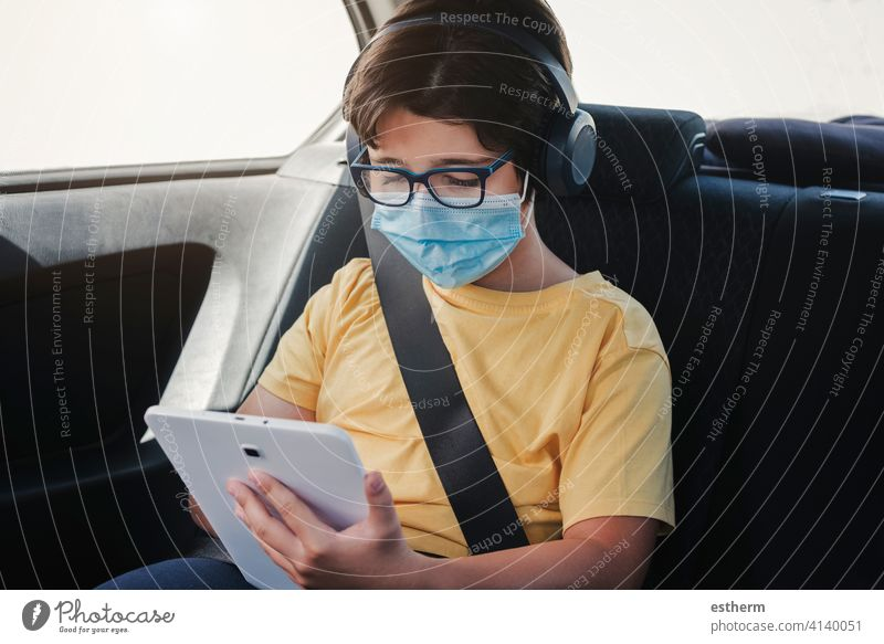 kid with medical mask riding in a car coronavirus tablet motor vehicle seatbelts security safety epidemic pandemic quarantine child family covid-19 trip travel