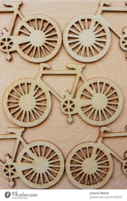 Wooden cutout bicycles on a wood background. Bicycle Wheels Transport Cycling bike biking Cycling tour transportation ride Pedal lifestyle cyclist travel