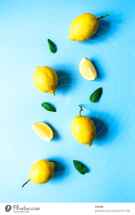 Lemons and peppermint on a blue background. Flat lay. Yellow Mature Blue background flat lay Sour Citrus fruits Juicy Vitamin Tropical naturally Green Organic