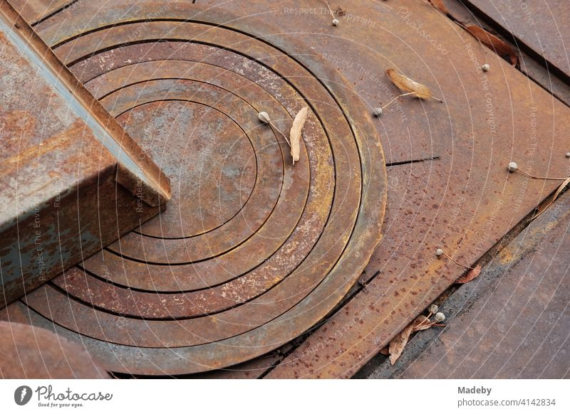 Rusty old stove plate with concentric circles of an old stove with grill in autumn outside on a farm in Rudersau near Rottenbuch in the district of Weilheim-Schongau in Upper Bavaria