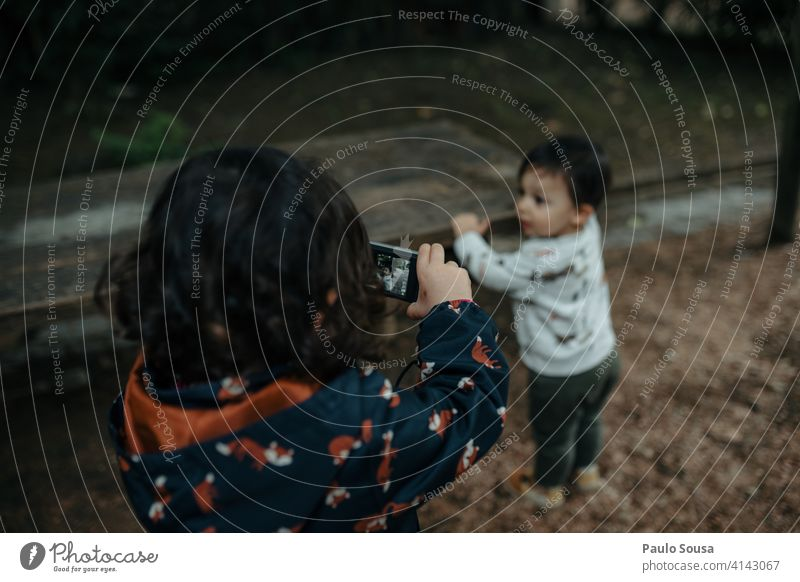 Young girl taking photo of her young brother Brothers and sisters Child 1 - 3 years Caucasian childhood Digital Digital photography Camera Technology Happy