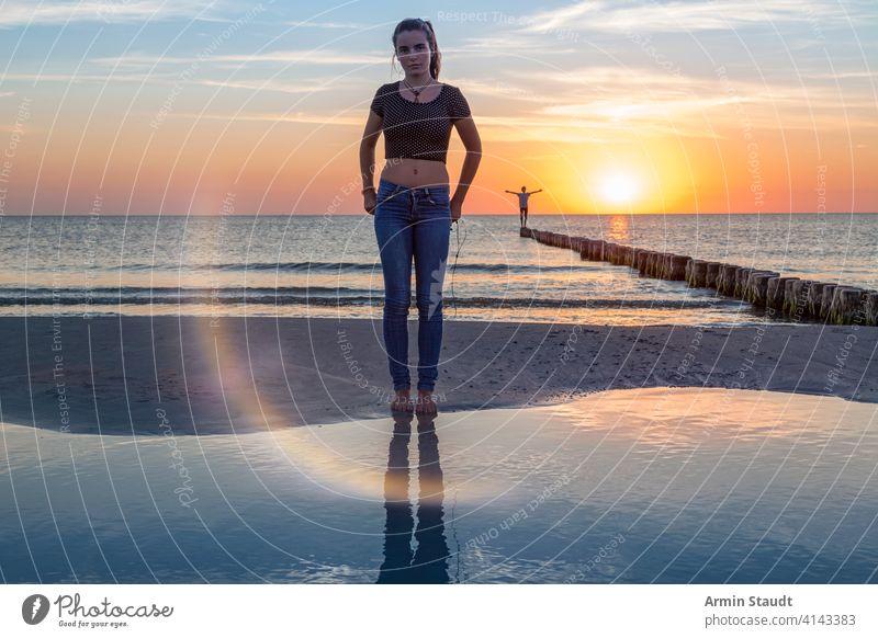 sunset over the baltic sea, portrait of a young woman standing on the beach balancing beautiful beauty boy dusk far freedom girl groin horizon idyllic jetty