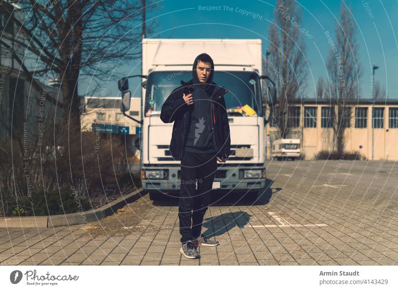 young man with backpack stands in front of a truck aeria architecture beautiful black boy building casual caucasian confident hoodie lifestyle looking lorry