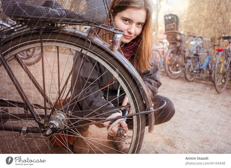 Young woman pumps up the tires of her bike activity air bicycle casual caucasian closeup confident crouching details equipment female fix girl lifestyle macro