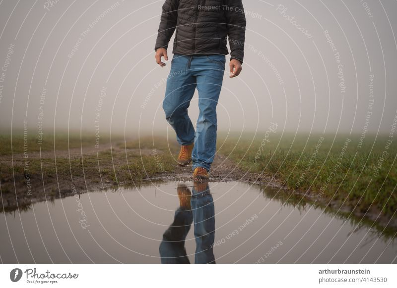 Young man walking in the fog in nature towards a puddle of water on one's own Going Man Nature Fog outdoor Puddle stroll reflection Hiking Water Meadow