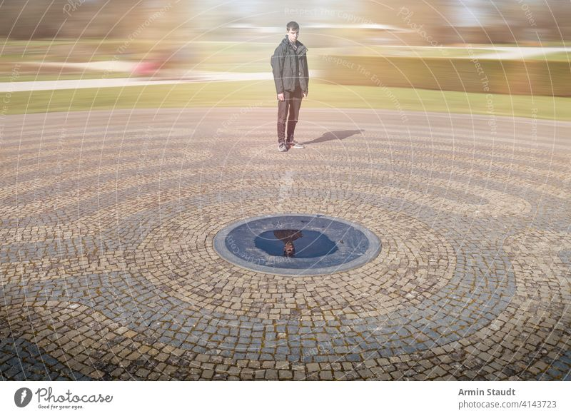 know thyself, young man in a moving world looking at his reflection adolescent adult awareness blur center circle concept confident consciousness contemplation