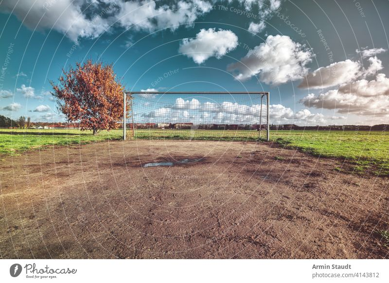 soccer goal with tree, skyline and cloudscape architecture autumn background ball berlin blue closeup competition empty europe fall field football game germany