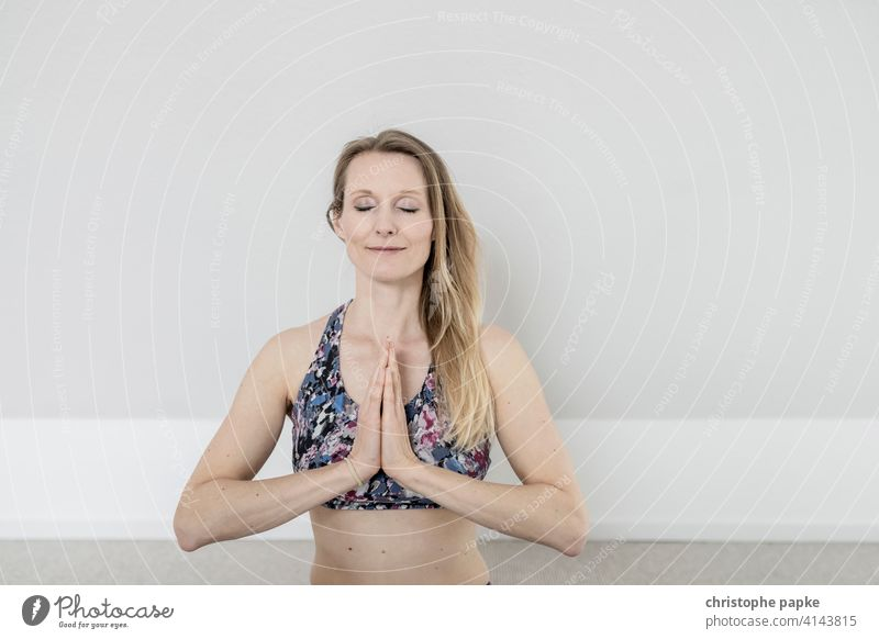 Woman does yoga at home Yoga Online Notebook Lifestyle Sports Athletic relaxation Mat Sit Blonde Leisure and hobbies Living room Interior shot Close-up