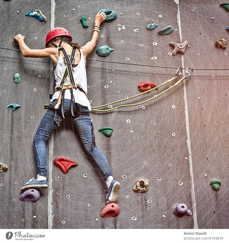 Teen Girl In A Free Climbing Wall active activity more adult Balance Bouldering ascent Climber tutorial Extreme Woman Fitness fun Hand Helmet hobby indoors