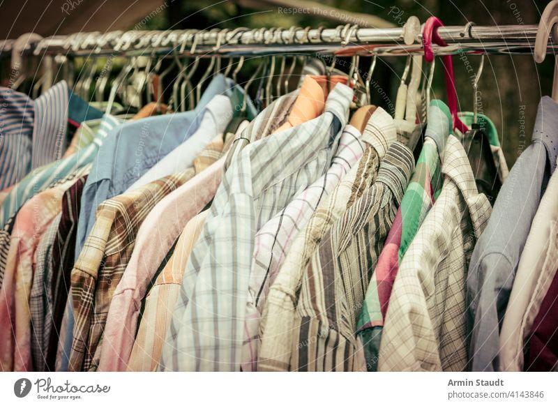 clothes on a rack on a flea market abundance car trunk sale casual clothes rack clothing coat colorfilter consumerism for sale garage sale garment hand me downs