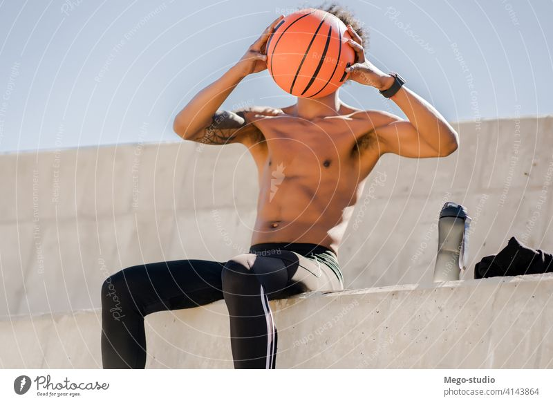 Afro athletic man relaxing after training. sport athlete basketball urban outdoor standing enjoy expression outdoors active hand exercise recreation sports