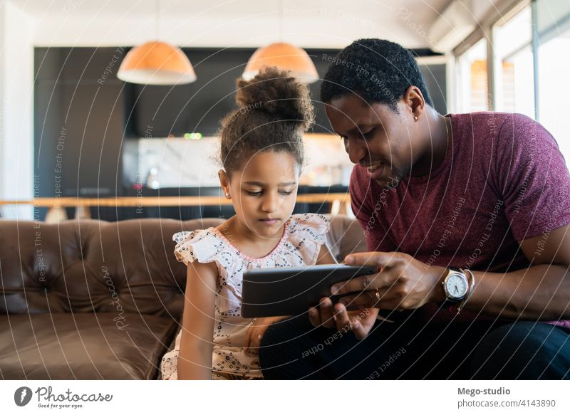 Father and daughter using digital tablet at home. father monoparental play lifestyle family single parent indoor activity parenting relationship daddy cute