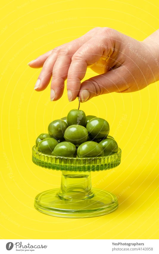 Woman hand taking a green olive. Eating fresh organic olives Olea europaea appetizer background close-up color colorful copy space cuisine cut out delicious