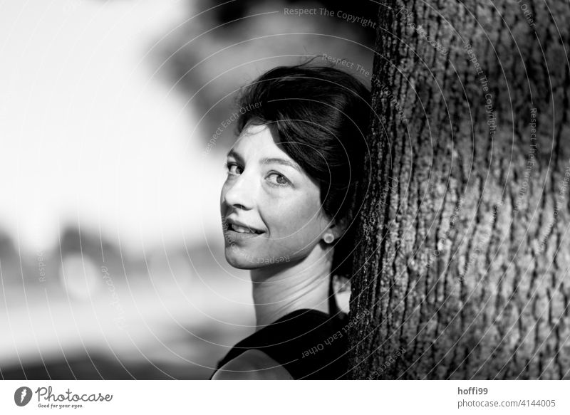 The woman leans relaxed against a tree and looks smiling into the camera Young woman Lean Women's eyes Tree trunk portrait Face of a woman Youth (Young adults)