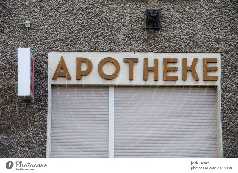 APOTHEKE in rural areas Pharmacy lettering house wall Gray Characters Entrance Pharmaceutics Signs and labeling Lightbox Roller shutter Weathered extractor hood