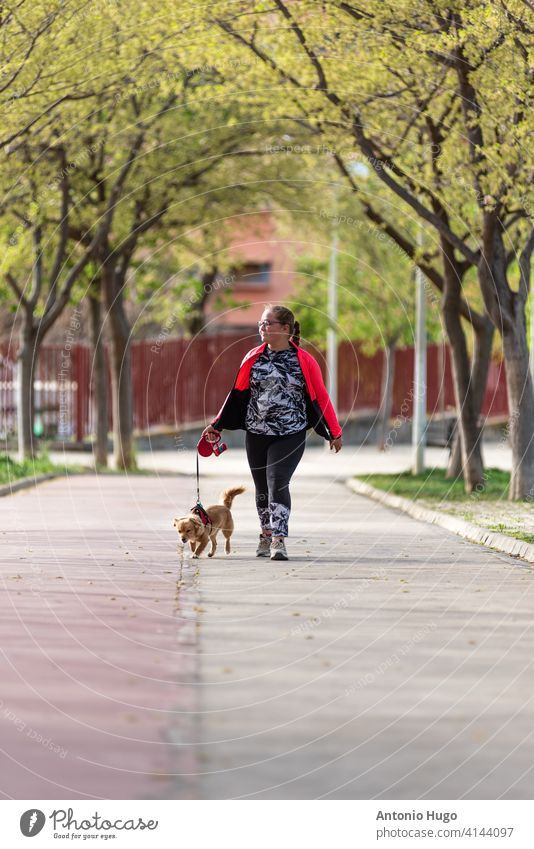 Chubby blonde girl with eyeglasses walking her dog in the park. chubby obese obesity canine friend owner fat pet animal kid childhood cute friendship happiness