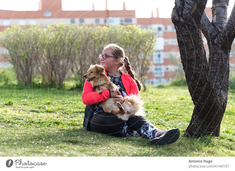 Portrait of a chubby blonde girl with eyeglasses sitting on the lawn with her dog. obese obesity portrait together grass park tree residential buildings mascot