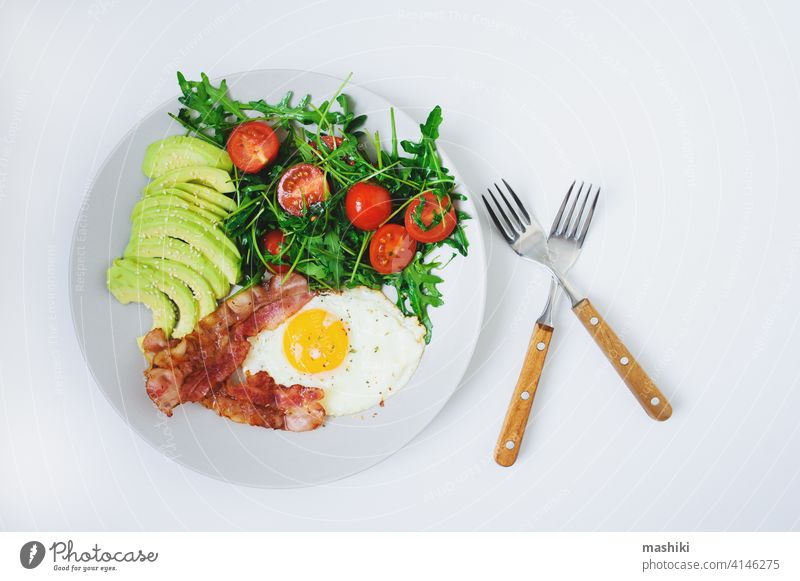 tasty breakfast - fried egg and bacon served with arugula tomato salad and fresh avocado on white plate food meal morning vegetable brunch organic