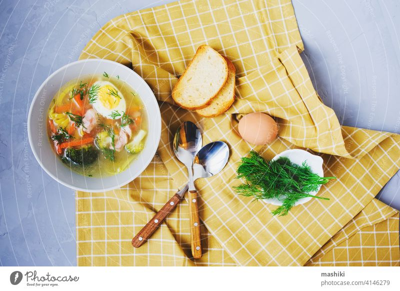 healthy homemade chicken noodle soup with egg, broccoli and carrot served in plate with toasted bread vegetable dinner food lunch meal meat bowl pasta delicious