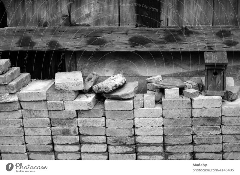Carefully and neatly stacked bricks in front of an old wooden barn on a farm in Rudersau near Rottenbuch in the district of Weilheim-Schongau in Upper Bavaria, photographed in classic black and white