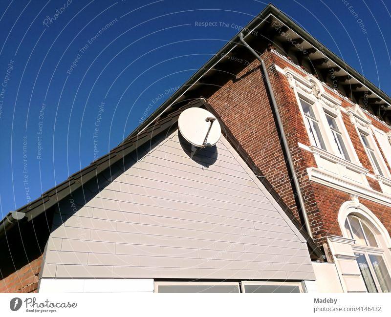 Satellitenschüsel im Spitzgiebel eines Nebengebäude vor einem schönen Altbau im Sonnenschein in Lemgo bei Detmold in Ostwestfalen-Lippe Satellitenschüssel