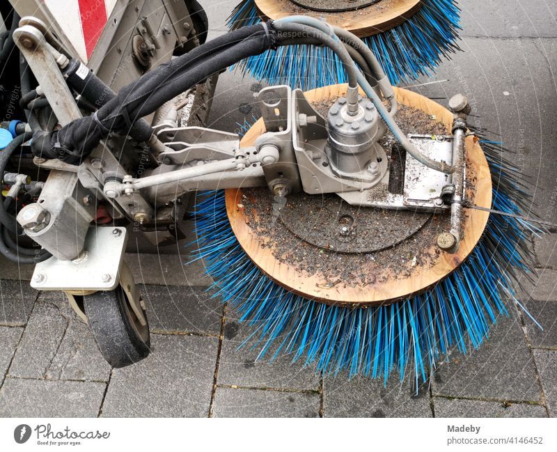 Sweeper with rotating blue bristles on a sidewalk in Offenbach am Main in Hesse, Germany Roadsweeper Bristles rotation Broom cleaning Street cleaning technique