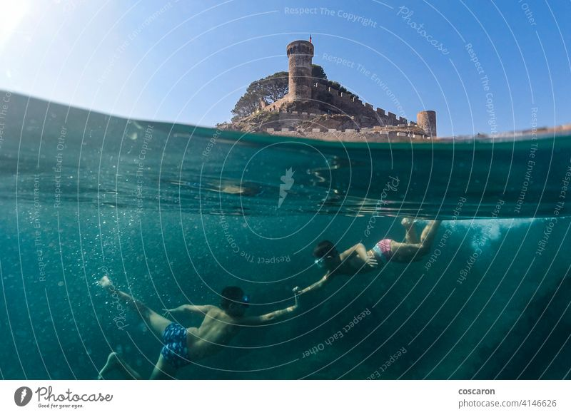 Two little boys snorkeling with a castle in the background apnea beach caribbean child childhood cute dive diver enjoying enjoyment exploration friends fun half